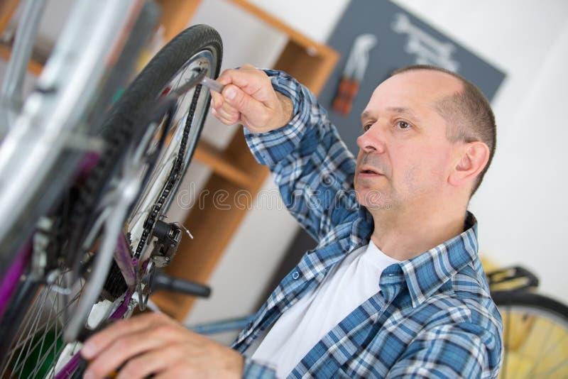 Hombre que fija una bici fotografía de archivo libre de regalías