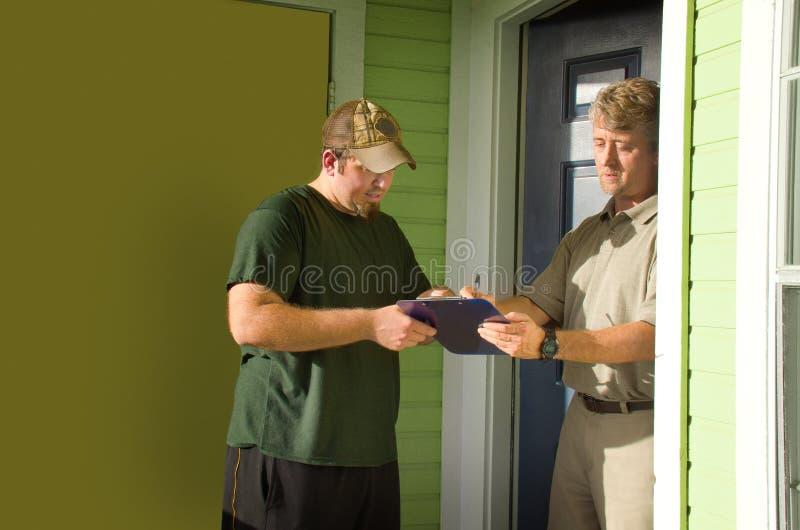 Hombre que firma encuesta o la petición a domicilio imagenes de archivo