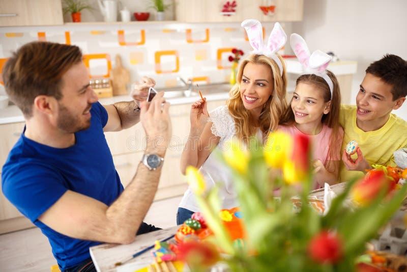 Hombre que fotografía a la familia mientras que pinta los huevos imagen de archivo