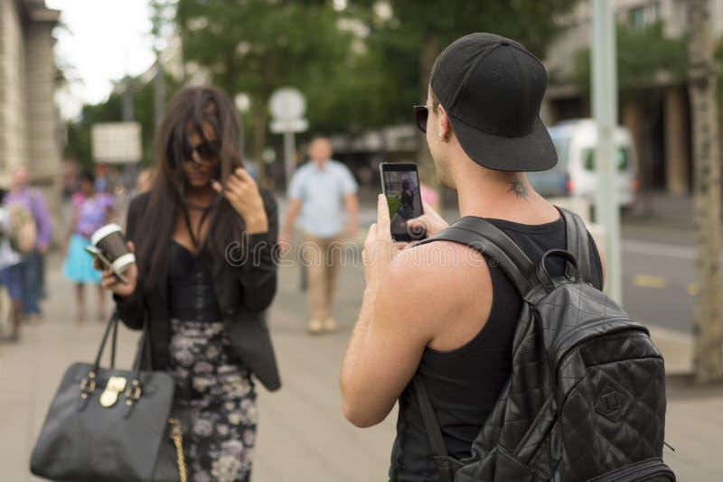 Hombre que fotografía a la muchacha en la calle imagen de archivo