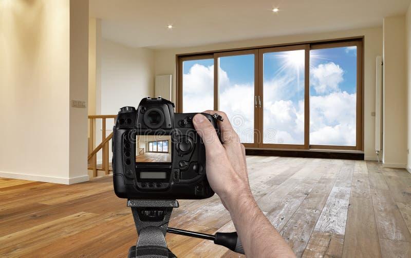 Hombre que fotografía la sala de estar vacía imagen de archivo