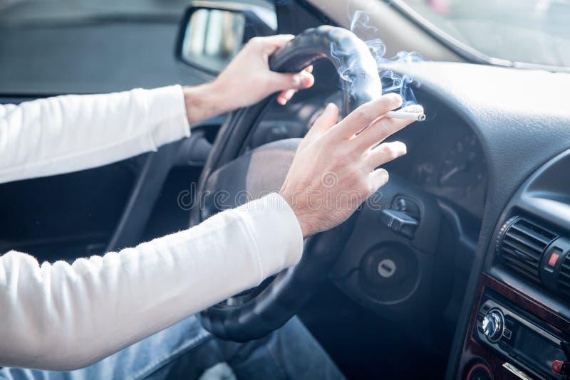 Hombre que fuma un cigarrillo en la rueda de un coche Conducción y el fumar foto de archivo