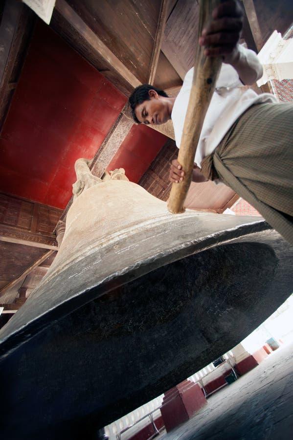 Hombre que golpea la campana de Mingun en Myanmar fotografía de archivo
