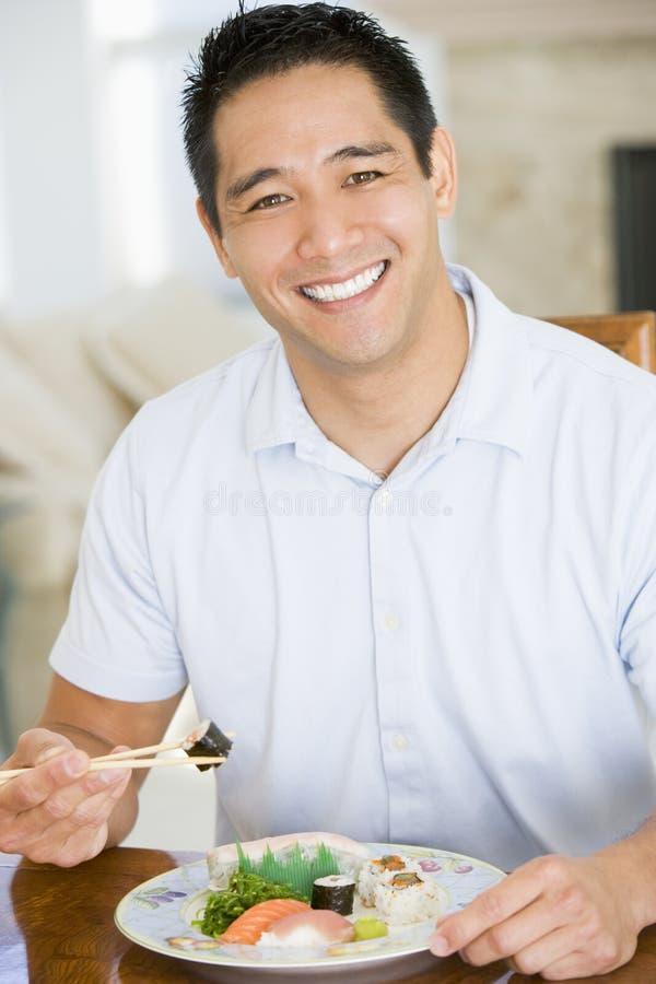 Hombre que goza del alimento chino con los palillos imagen de archivo