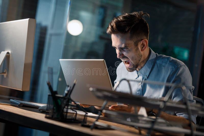 Hombre que grita en el ordenador portátil quebrado fotografía de archivo libre de regalías