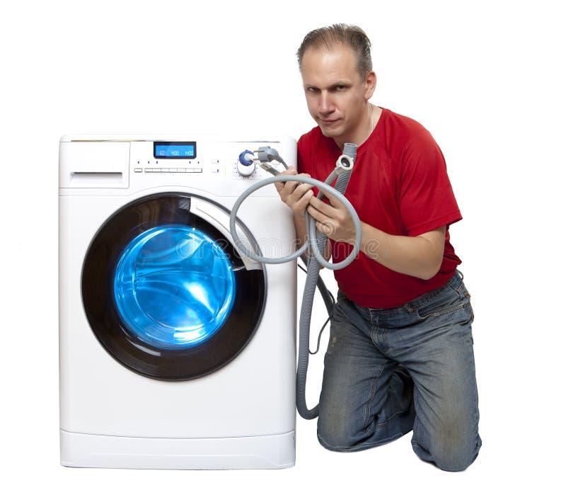 Hombre que ha pensado en la reparación o la conexión de la lavadora cerca de la nueva lavadora imagen de archivo