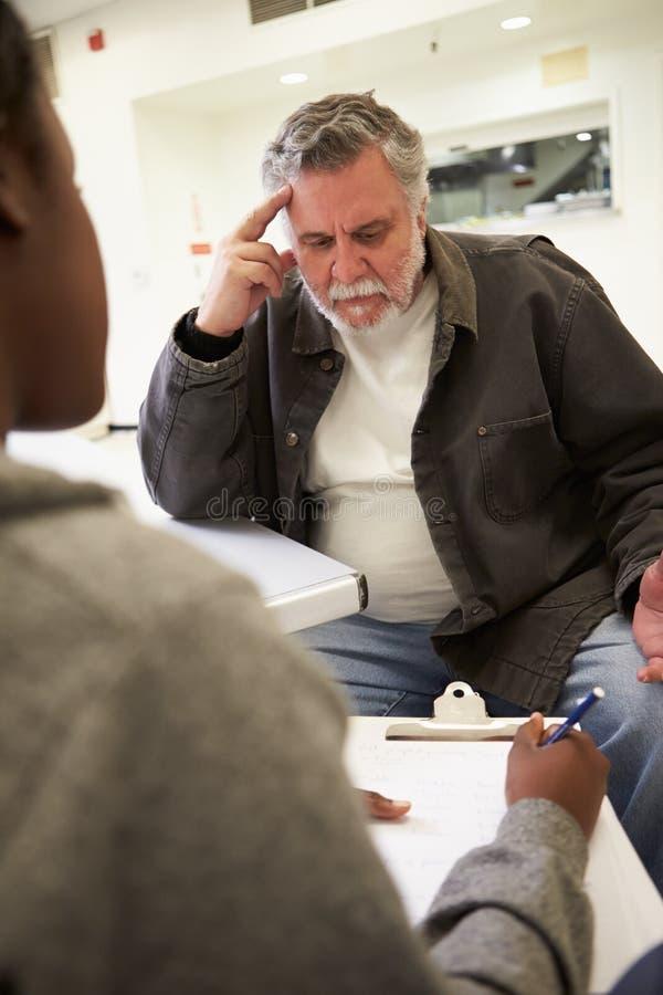 Hombre que habla con el consejero que toma notas fotografía de archivo libre de regalías