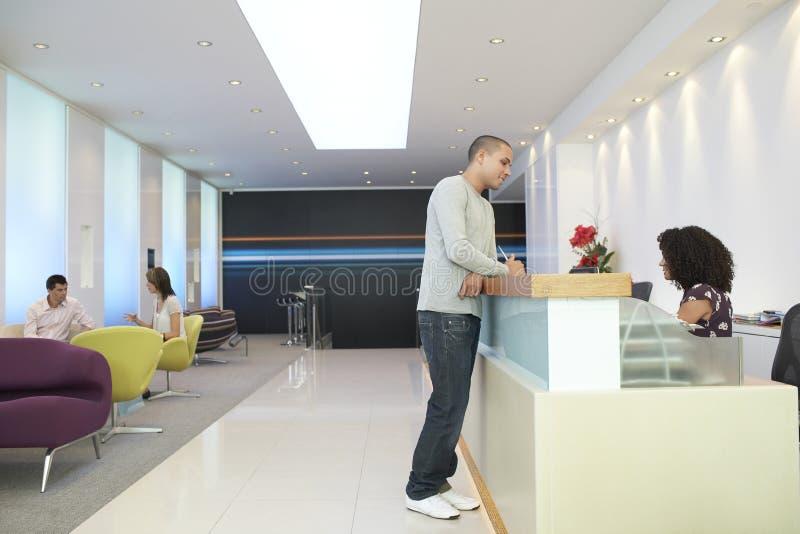 Hombre que habla con el recepcionista At Office imagen de archivo
