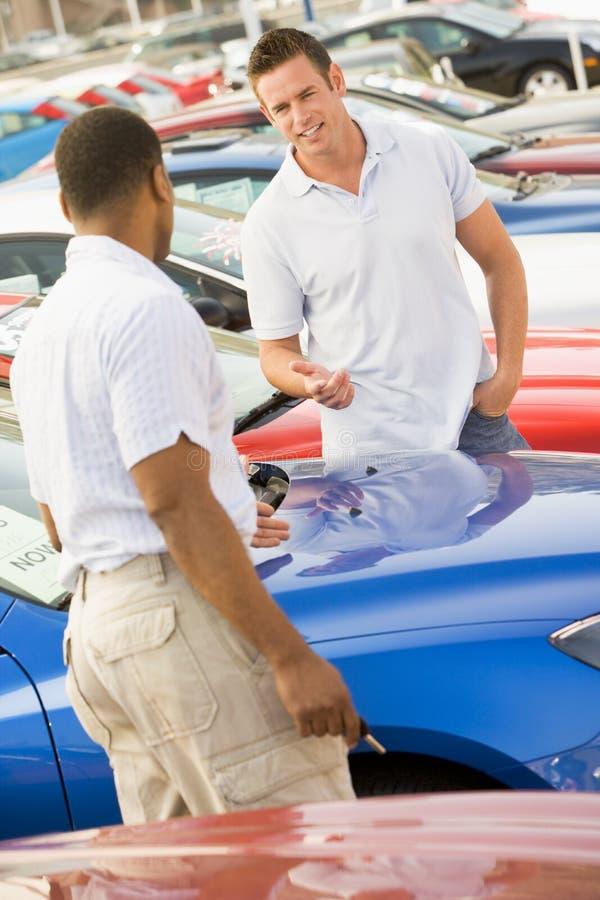 Hombre que habla con el vendedor de coche foto de archivo libre de regalías