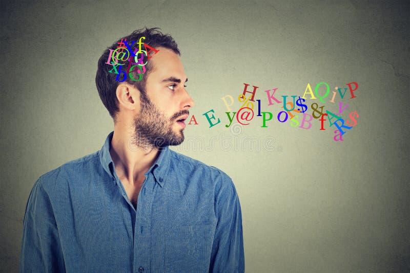 Hombre que habla con las letras del alfabeto en su cabeza y que sale de la boca abierta fotos de archivo