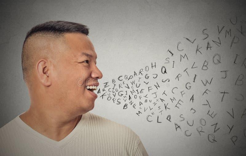 Hombre que habla con las letras del alfabeto que salen de la boca abierta fotos de archivo