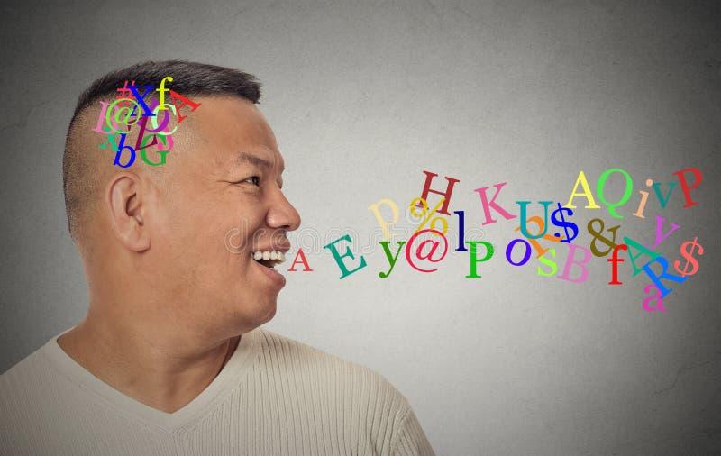 Hombre que habla con las letras del alfabeto que salen de la boca abierta imagen de archivo libre de regalías