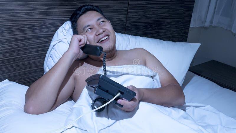 Hombre que habla en el teléfono a la medianoche imagenes de archivo