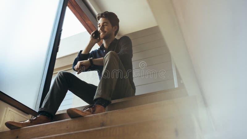 Hombre que habla sobre el teléfono móvil que se sienta en casa fotos de archivo libres de regalías