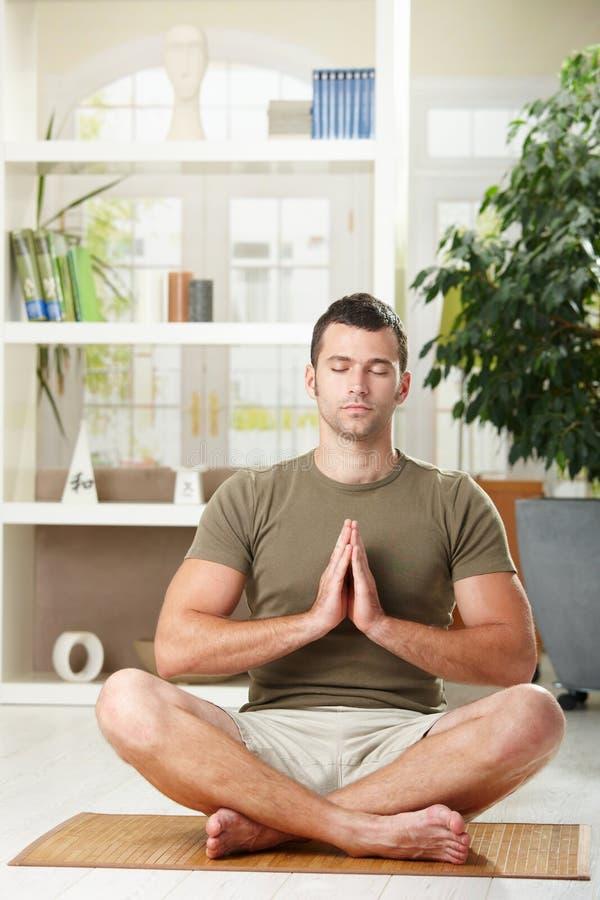 Hombre que hace ejercicio de la yoga foto de archivo
