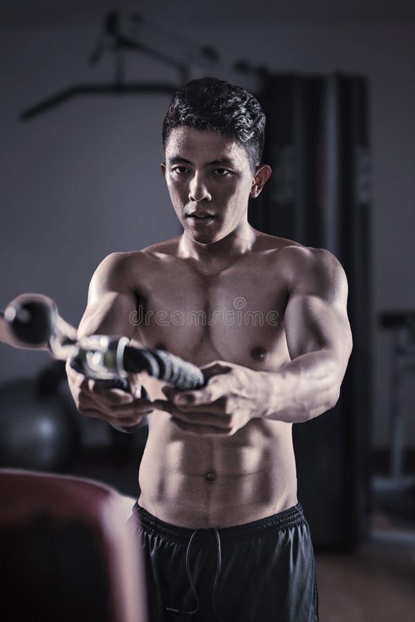 Hombre que hace ejercicios con el equipo de la aptitud foto de archivo