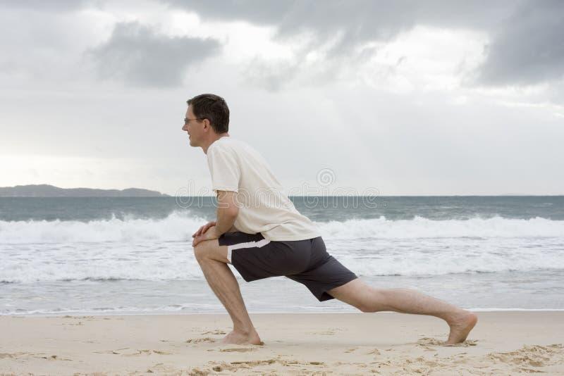 Hombre que hace ejercicios de la aptitud en una playa imagen de archivo