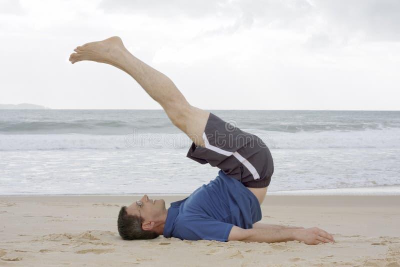 Hombre que hace ejercicios de la aptitud en una playa imagen de archivo libre de regalías