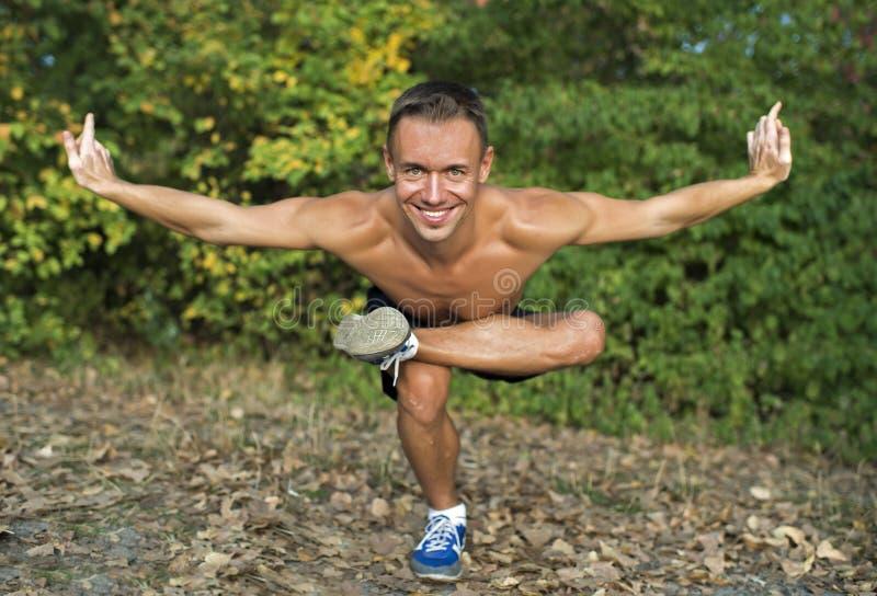 Hombre que hace ejercicios de la yoga en el parque foto de archivo