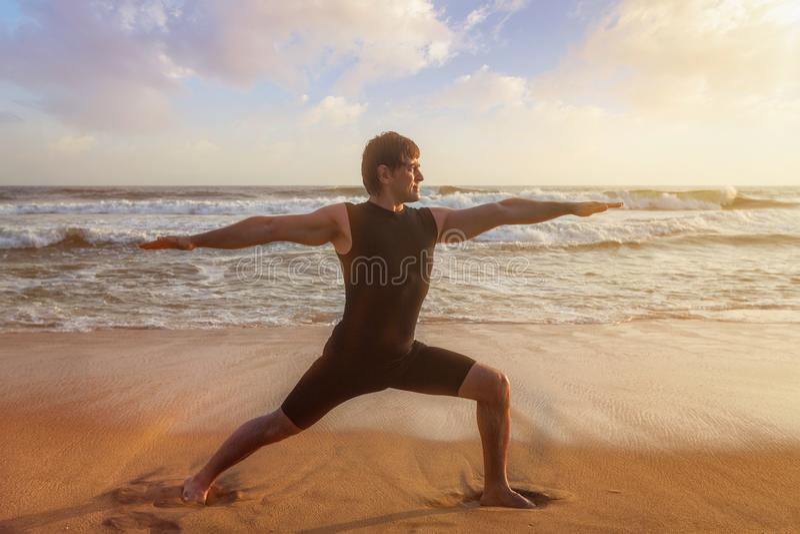 Hombre que hace el asana Virabhadrasana de la yoga 1 actitud del guerrero en la playa imagen de archivo