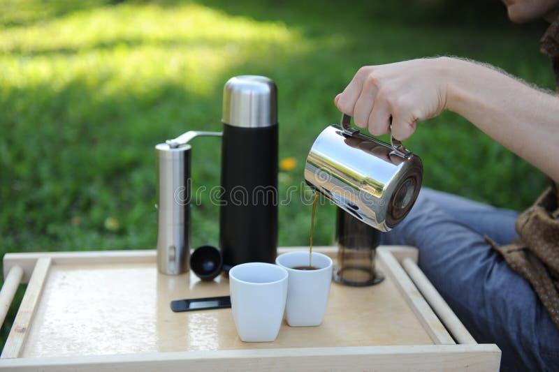 Hombre que hace el café en naturaleza imagenes de archivo