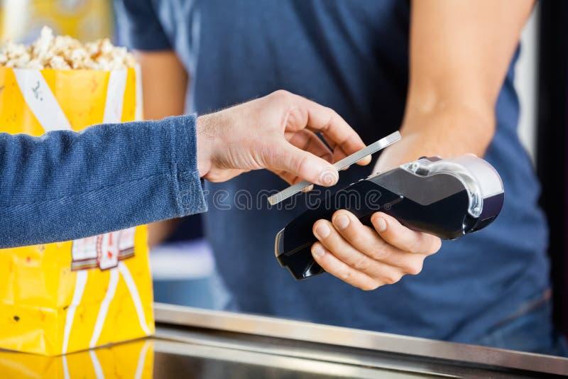 Hombre que hace el pago con tecnología de NFC en imagenes de archivo