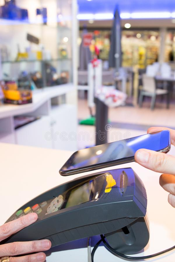 Hombre que hace el pago para la transacción de la compra con su teléfono móvil Nfc sin contacto imagen de archivo libre de regalías