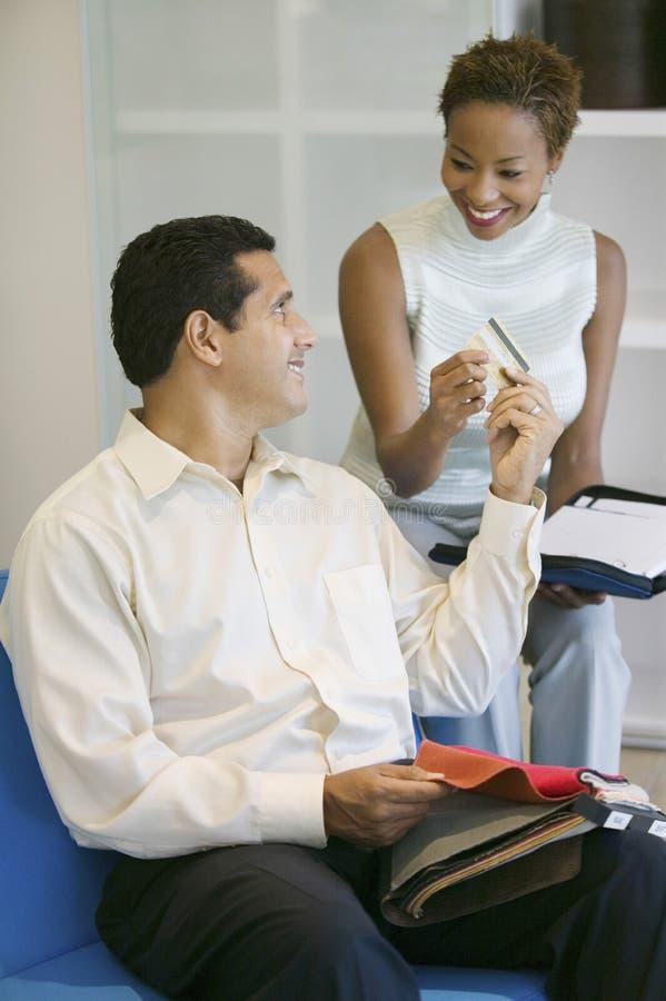 Hombre que hace el pago a través de tarjeta de crédito en tienda foto de archivo