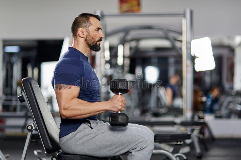 Hombre que hace el rizo del bíceps en el gimnasio fotografía de archivo