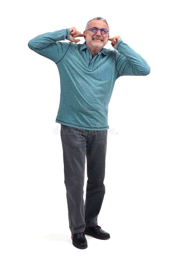 Hombre que hace el ruido que daña sus oídos en el fondo blanco fotos de archivo