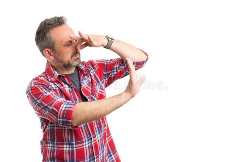Hombre que hace gesto de la parada como sostener la nariz imagenes de archivo