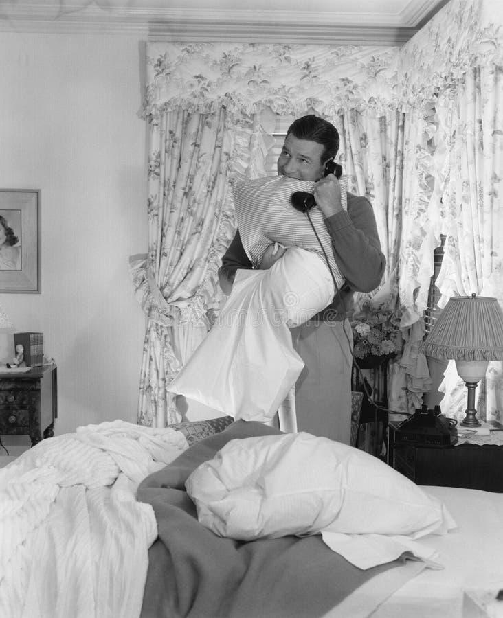 Hombre que hace la cama y que habla en el teléfono foto de archivo libre de regalías