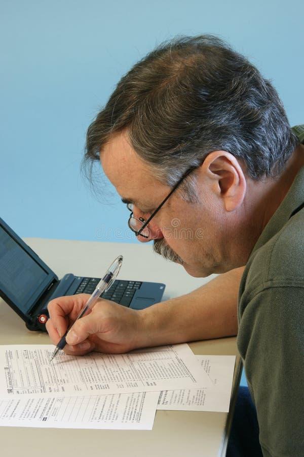 Hombre que hace la forma federal del impuesto sobre la renta 1040 imagen de archivo