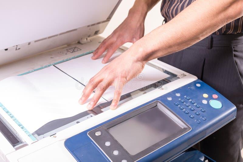 Hombre que hace la fotocopia usando la copiadora en oficina imagen de archivo libre de regalías