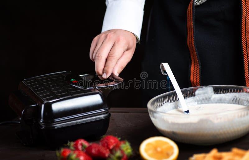 Hombre que hace las galletas en una máquina de la galleta imagen de archivo