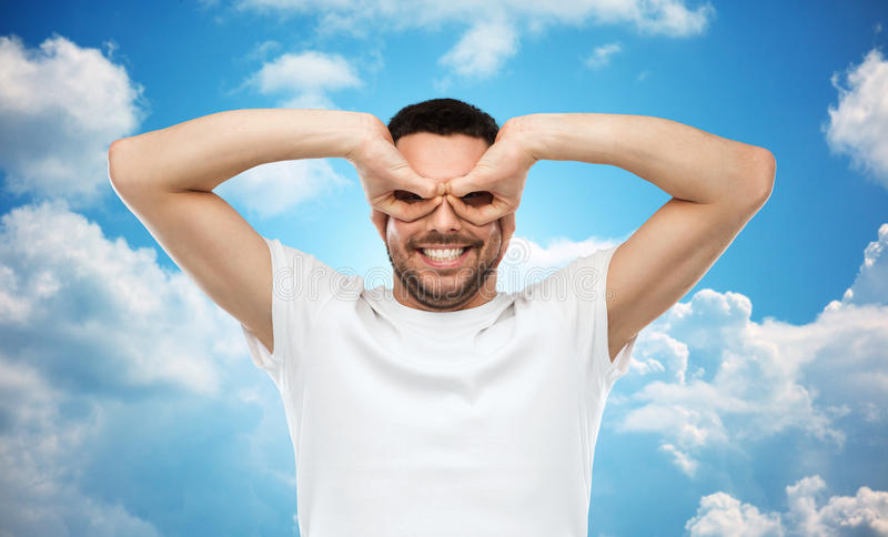 Hombre que hace los vidrios de finger sobre fondo del cielo fotos de archivo