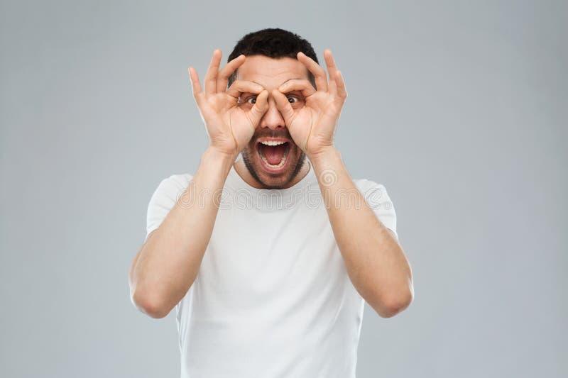 Hombre que hace los vidrios de finger sobre fondo gris imagen de archivo