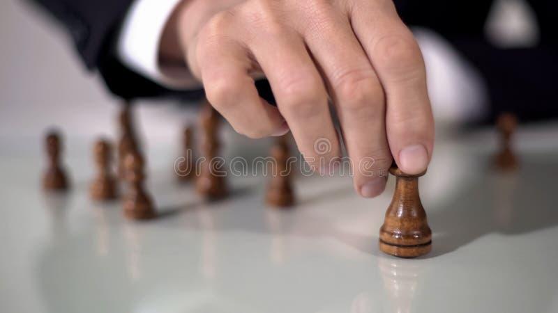Hombre que hace movimiento de la reina que gana en juego de ajedrez, usando estrategia empresarial acertada foto de archivo