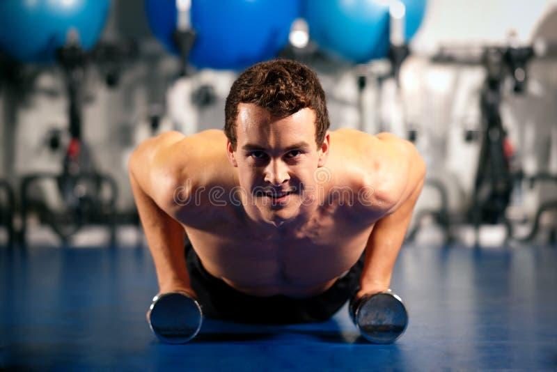 Hombre que hace pectorales en gimnasia fotos de archivo