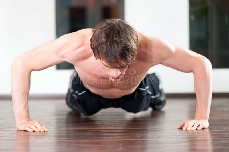 Hombre que hace pectorales en gimnasia foto de archivo libre de regalías