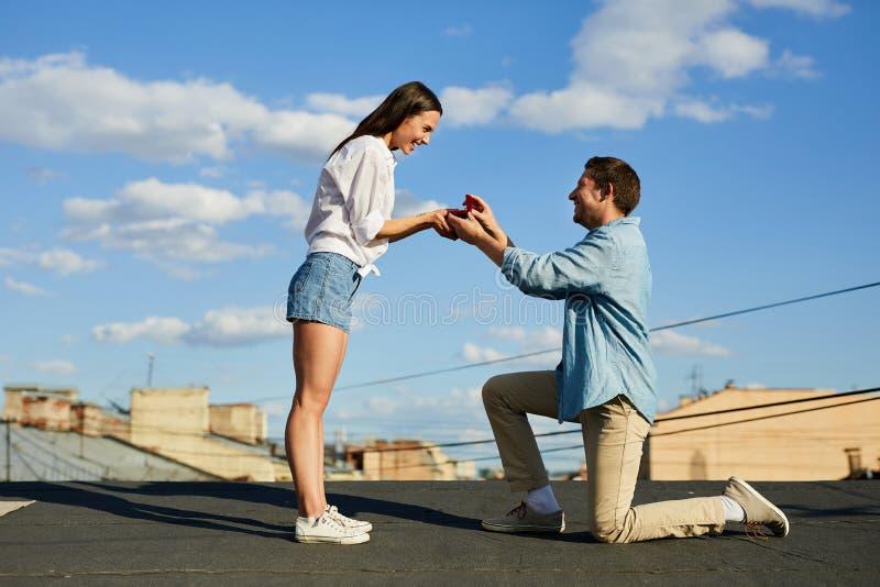 Hombre que hace propuesta de matrimonio en el tejado fotos de archivo