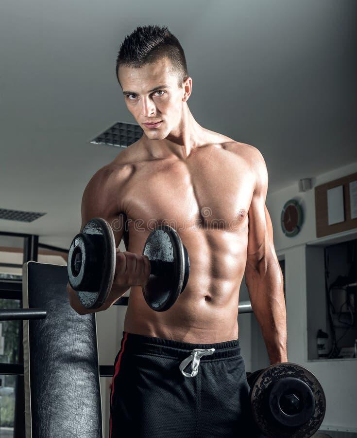 Hombre que hace rizos del bíceps imagen de archivo libre de regalías