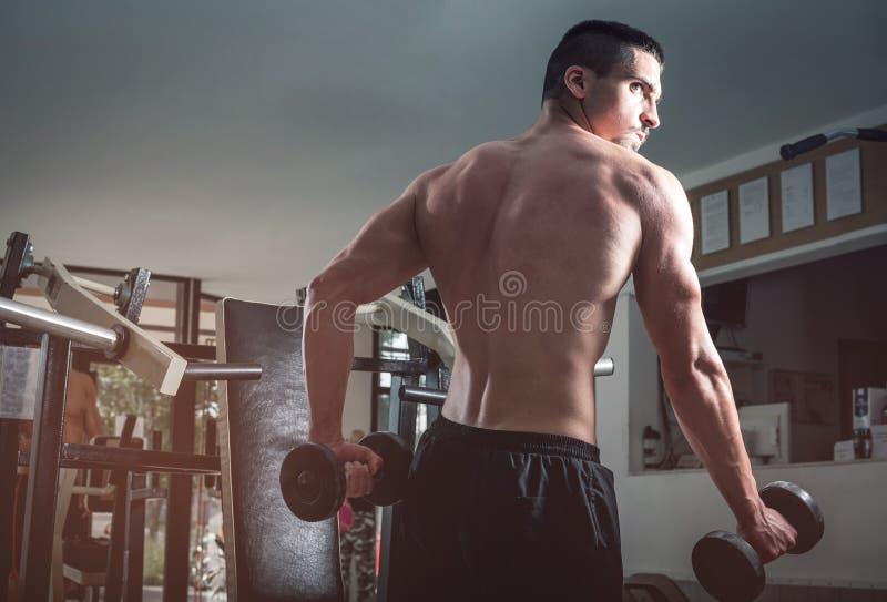 Hombre que hace rizos del bíceps imagen de archivo