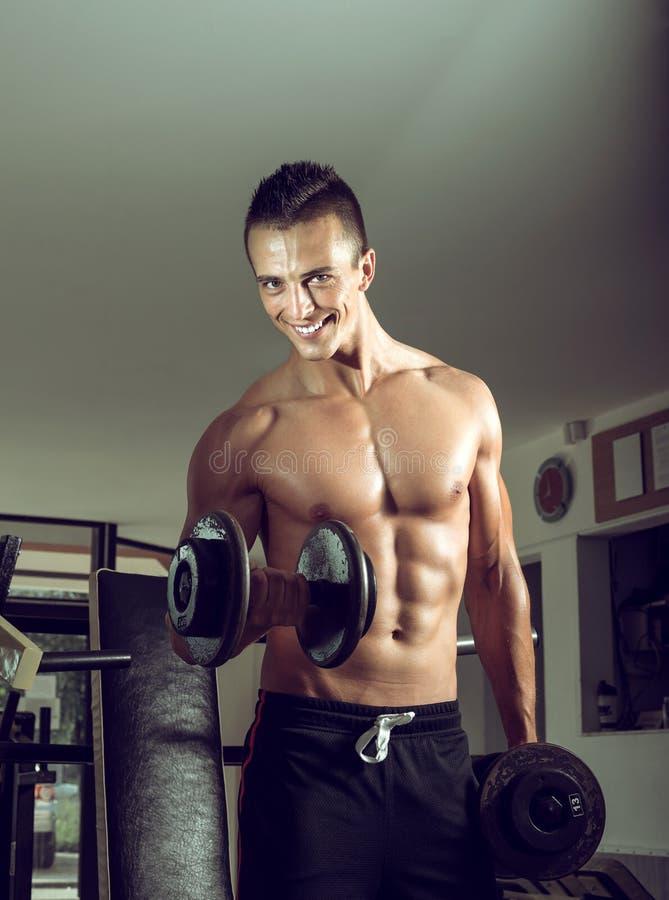 Hombre que hace rizos del bíceps imagenes de archivo
