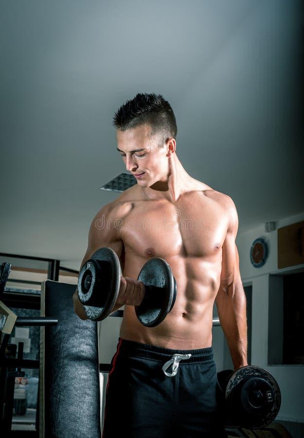 Hombre que hace rizos del bíceps foto de archivo libre de regalías