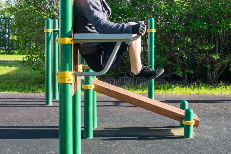 Hombre que hace un ejercicio, en barras desiguales, aire libre, vista lateral, primer imagenes de archivo
