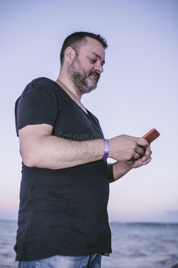 Hombre que hace una foto en la playa fotografía de archivo
