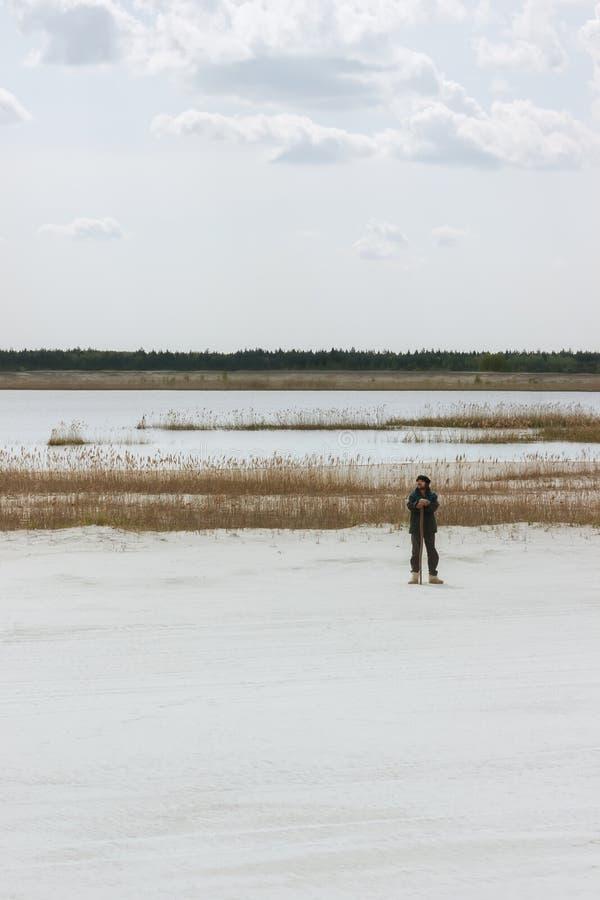 Hombre que hace una pausa el lago entre la arena blanca del cuarzo imagenes de archivo