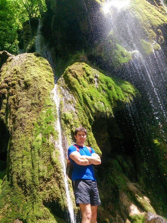 Hombre que hace una pausa la cascada hermosa en Rumania imagenes de archivo