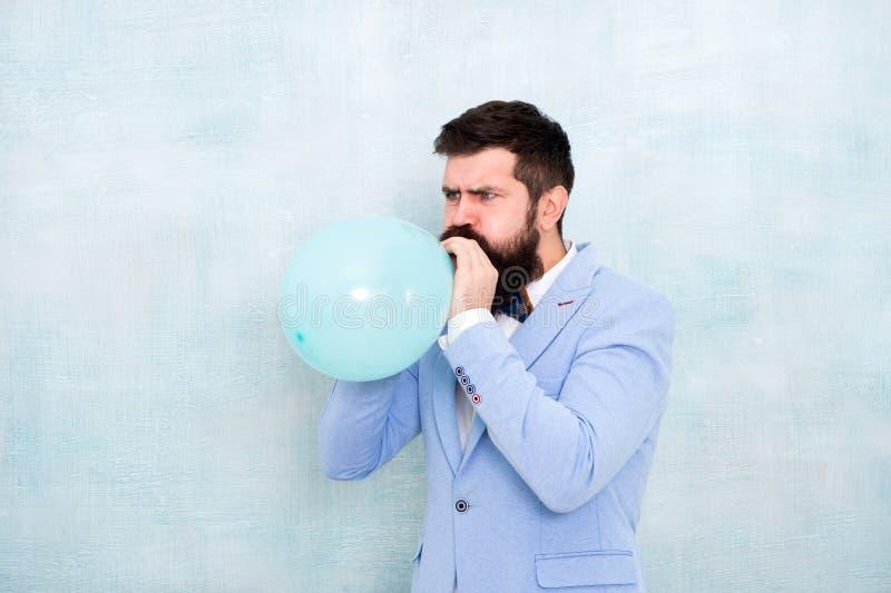 Hombre que infla un globo azul Hombre barbudo con el globo Feliz cumpleaños preparación a ir de fiesta, celebración Praparation imágenes de archivo libres de regalías